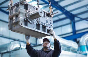 Engineer using crane to move industrial gearbox to paint works in engineering factoryの写真素材 [FYI03510171]