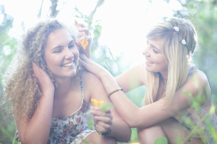 Two teenage girls with wildflowers in woodlandの写真素材 [FYI03510239]