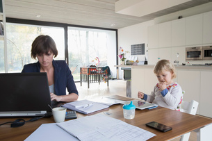 Mother with female toddler working on computer at kitchen tableの写真素材 [FYI03510357]