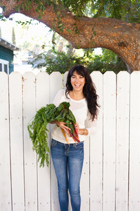 Portrait of young woman holding homegrown vegetablesの写真素材 [FYI03510362]