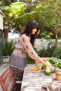 Young woman with vegetables on tableの写真素材 [FYI03510367]