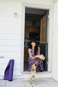 Young woman sitting in doorway with dogの写真素材 [FYI03510371]