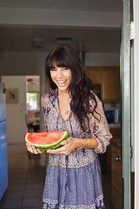 Young woman in doorway holding watermelonの写真素材 [FYI03510372]