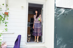 Young woman in doorway with vegetable juiceの写真素材 [FYI03510373]