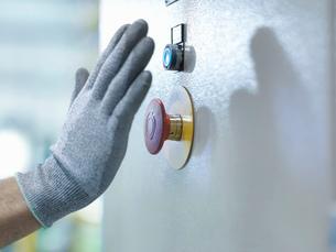 Engineer pressing emergency stop in engineering factory, close upの写真素材 [FYI03510381]
