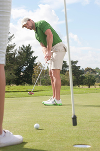 Young male golfer putting on golf greenの写真素材 [FYI03510617]