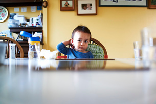 Baby boy sitting at kitchen tableの写真素材 [FYI03510622]