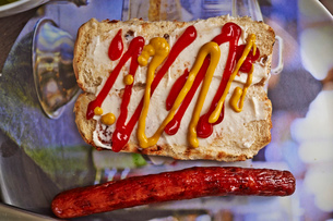 Still life of bread bun, mustard, tomato sauce and a hot dog sausageの写真素材 [FYI03510626]