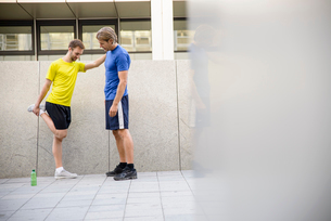 Man stretching with hand on man's shoulderの写真素材 [FYI03510910]