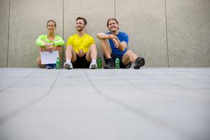 Three friends sitting on floor wearing sports clothingの写真素材 [FYI03510911]