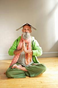 Senior man in lotus position with laptop on headの写真素材 [FYI03510939]
