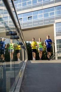 Small group of adult runners crossing city footbridgeの写真素材 [FYI03511138]