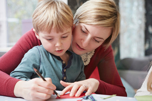 Mother and son drawing at kitchen tableの写真素材 [FYI03511316]