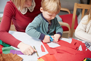 Mother and son craft making at kitchen tableの写真素材 [FYI03511317]