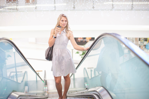 Young woman going up escalator in mallの写真素材 [FYI03511643]