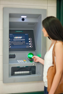 Young woman withdrawing money at cash machineの写真素材 [FYI03511655]