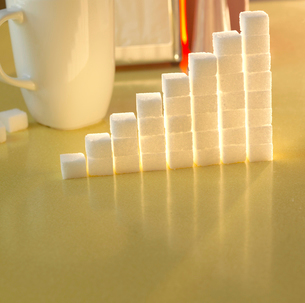 Stack of sugar cubes in the shape of a graph on a yellow tableの写真素材 [FYI03511888]