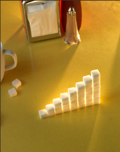 Stack of sugar cubes in the shape of a graph on a yellow tableの写真素材 [FYI03511889]