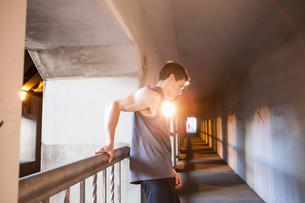 Young male runner taking a break on urban bridgeの写真素材 [FYI03511898]