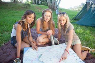 Three young females friends planning route whilst campingの写真素材 [FYI03511924]