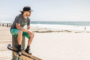 Young man sitting on wooden post, Laguna Beach, California, USAの写真素材 [FYI03512144]