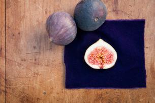 Still life of three figs, one sliced in half on purple clothの写真素材 [FYI03512185]