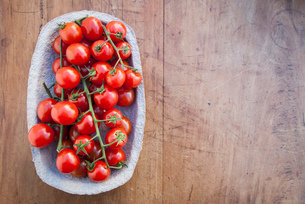 Still life of cherry vine tomatoes in cardboard containerの写真素材 [FYI03512188]