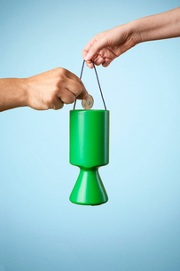Studio shot of hand putting coin into charity collection boxの写真素材 [FYI03512287]