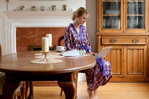 Young woman at home in dressing gown working on laptopの写真素材 [FYI03512451]