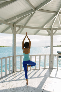 Young woman practicing yoga tree pose in coastal gazebo, Providenciales, Turks and Caicos Islands, Cの写真素材 [FYI03512459]