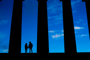A young couple hold hands on the National Monument of Scotland on Calton Hill in Edinburghの写真素材 [FYI03512701]