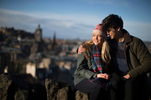 A young couple hug on Calton Hill with the background of the city of Edinburgh, capital of Scotlandの写真素材 [FYI03512702]