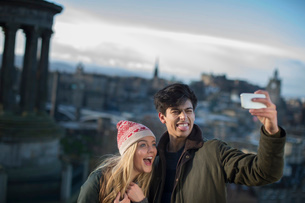 A young couple photograph themselves on Calton Hill with the background of the city of Edinburgh, caの写真素材 [FYI03512703]