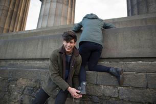 A young man helps his girlfriend climb onto the National Monument on Calton Hill in Edinburgh, Scotlの写真素材 [FYI03512716]