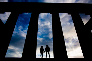 A young couple hold hands at the National Monument on Calton Hill in Edinburgh, Scotlandの写真素材 [FYI03512717]