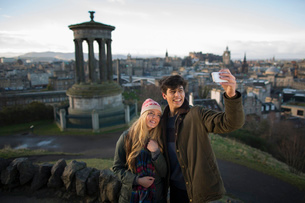 A young couple photograph themselves on Calton Hill with the background of the city of Edinburgh, caの写真素材 [FYI03512722]