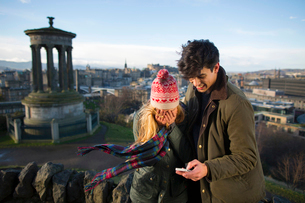 A young couple photograph themselves on Calton Hill with the background of the city of Edinburgh, caの写真素材 [FYI03512723]