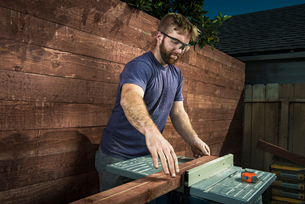 Joiner in backyard lining up planks of wood on workbenchの写真素材 [FYI03512796]