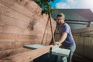 Joiner in backyard measuring planks of wood on workbenchの写真素材 [FYI03512797]
