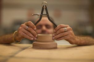 Close up of carpenter measuring turning wood in workshopの写真素材 [FYI03512844]