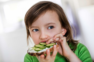 Girl eating a cheese and cucumber open sandwichの写真素材 [FYI03512918]