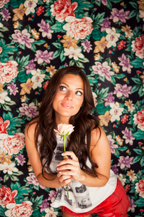 Young woman holding rose in front of floral wallpaperの写真素材 [FYI03513048]