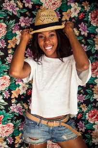 Young woman wearing straw hat in front of floral wallpaperの写真素材 [FYI03513051]