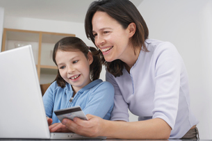 Mother and young daughter shopping onlineの写真素材 [FYI03513244]