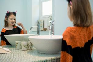 Girl in fancy dress costume brushing her teethの写真素材 [FYI03513249]