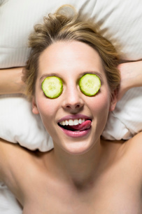 Young woman with cucumber slices covering eyesの写真素材 [FYI03513343]