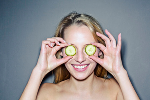 Young woman with cucumber slices covering eyesの写真素材 [FYI03513345]