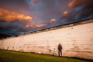 Young man standing next to white wall with his bicycleの写真素材 [FYI03513518]