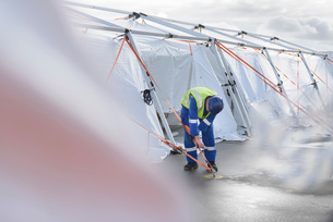Emergency Response Team worker adjusting tent anchorの写真素材 [FYI03513635]