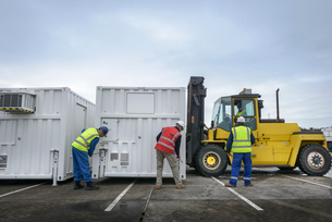 Emergency Response Team workers installing emergency control rooms with fork lift truckの写真素材 [FYI03513642]